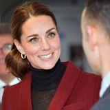 Herzogin Catherine zeigt sich an diesem Tag ebenfalls mit einem Zopf - sie trägt ihn jedoch mit einem leichten Seitenscheitel, ihre untere Haarpartie ist gelockt. Absoluter Hingucker ist jedoch ihre Haarschleife ...