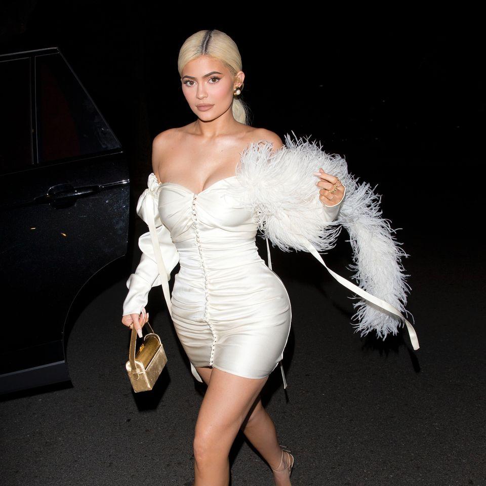 Sexy Schneekönigin! Paparazzi erwischen Kylie Jenner beim Verlassen einer Party in Los Angeles und halten den verführerischen Look der Make-up-Queen fest: Denn die 21-Jährige hüllt ihre sexy Kurven in ein hautenges und schulterfreies Mini-Kleid . Das goldene Handtäschchen und das Feder-Accessoire ziehen außerdem dieBlicke auf sich. Ein Outfit, das zu sexy für eine Mama ist? Fans im Netz zeigen sich verwundert über Kylies freizügigen Look und wollen sie lieber bekleideter sehen.