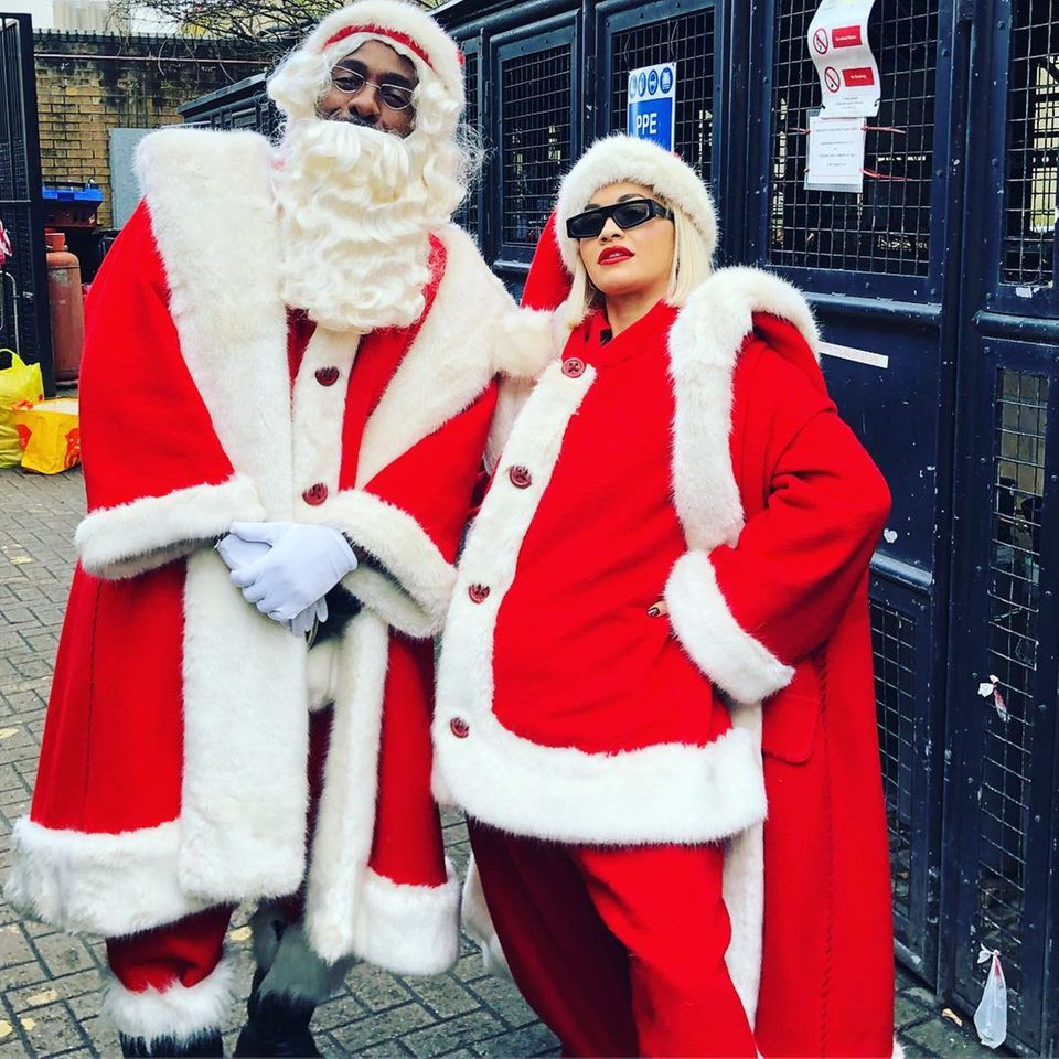 In diesen Weihnachtsmann-Kostümen stecken Idris Elba und Rita Ora, die sich so verkleidet auf den Weg zu einem Kinderkrankenhaus machen, um dort Geschenke zu verteilen.