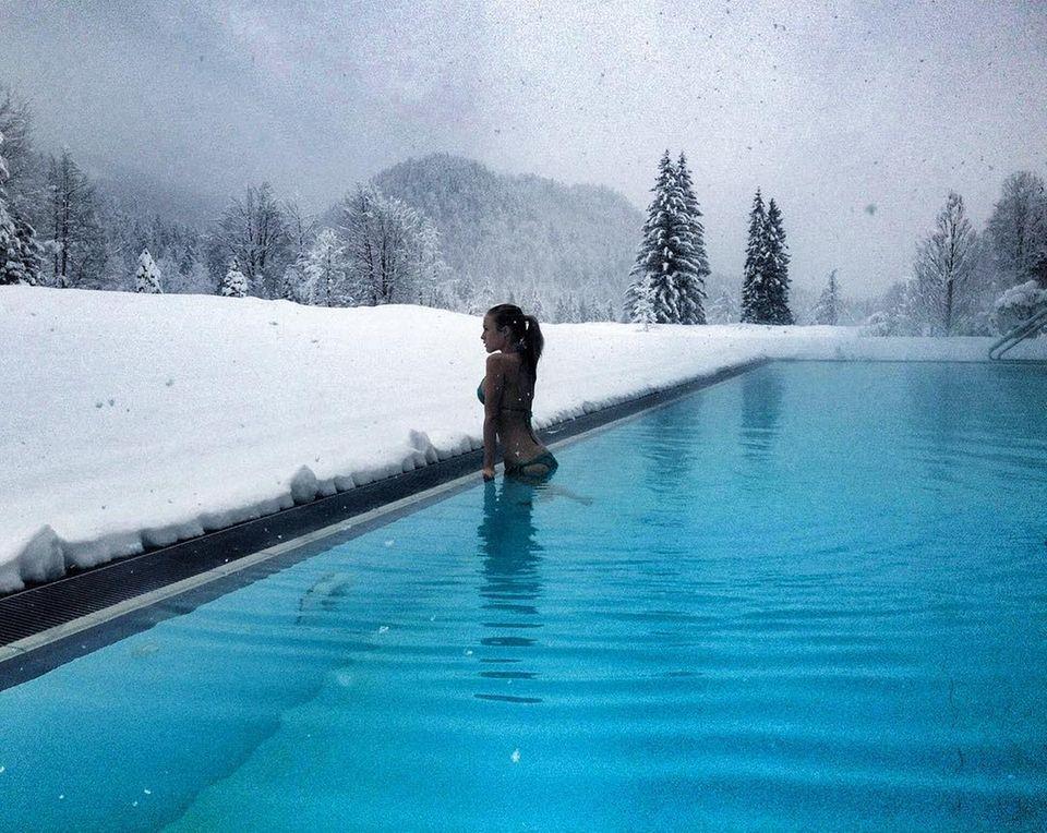 Aufgetaucht! In einer traumhaft schönenWinterlandschaft zieht Alena Fritz im gut beheizten Außenpool ihre Bahnen. Beim Auftauchen aus dem kristallklaren Wasser präsentiert sie ihren Modelkörper im knappen Bikini und hält diesen Moment mit einem Schnappschuss auf Instagram fest.
