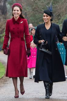 Catherine bevorzugt den weihnachtlich festlichen Style mit weinrotem und samt-besetztem Mantel mit farblich perfekt abgestimmten Accessoires, Meghan hingegen zeigt sich ganz in Schwarz, etwas extravaganter allerdings mit schwarzen Lederstiefel und zwei Federn am stylischen Pillbox-Hut.