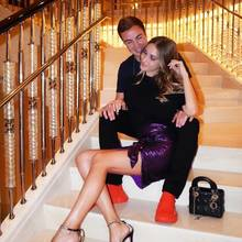 """Date-Night in Dubai: Ann-Kathrin und MarioGötze sind ohne Frage ein echtes Style-Couple. Zu ihrem violetten Metallic-Minirock kombiniert die schöne Influencerin eins schlichtes Oberteil und eine dazu farblich passende """"Lady Dior""""-Bag. Genau wie Mario setzt sie zudem auf Statement-Schuhe. Sowohl die knallroten Sneaker von ihm, als auch die funkelnden Sandaletten von ihr sind echte Hingucker."""