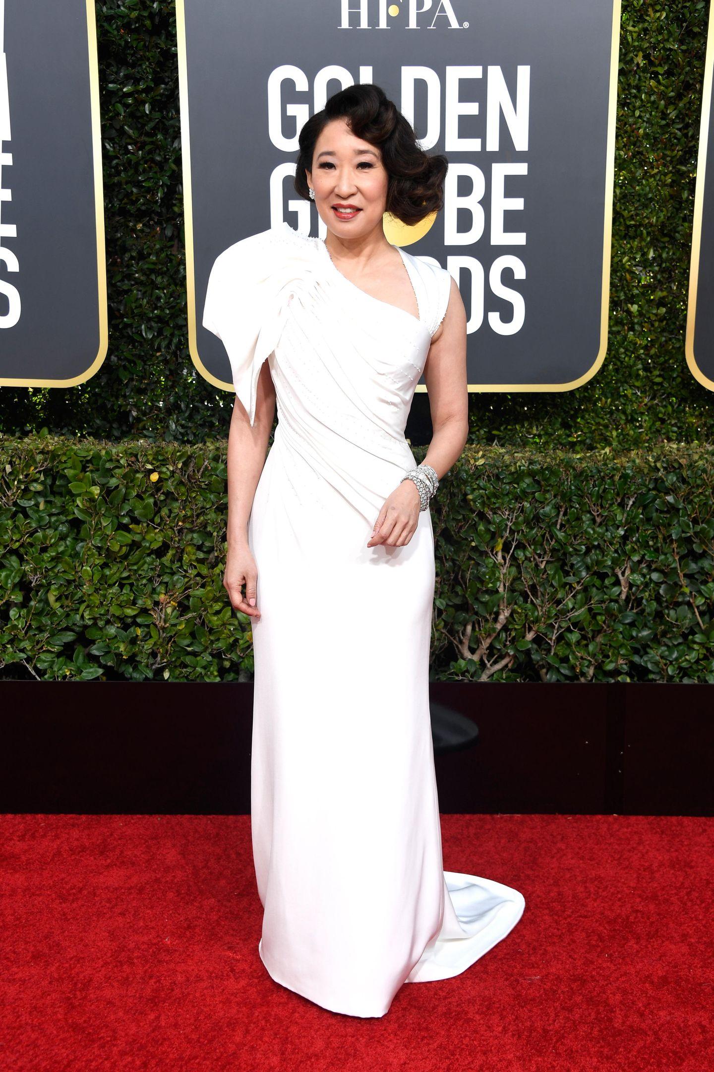Sandra Oh wird an der Seite von Andy Sambergdurch den Abend führen. Sie ist die erste Kanadierin, der diese Ehre zuteil wird. Zu diesem Anlass wird sie sich mehrfach umziehen. In einem weißen Versace Dress gelingt ihr allerdings schonmal ein grandioser Auftakt.