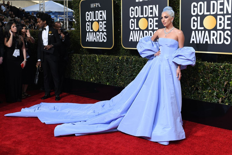 Gaga ist zurück! Die schauspielernde Sängerin zeigt sich in einem Cinderella-Kleid der Marke Valentinound hat zudem ihre Haare im selben Eisblau gefärbt.Der prachtvolle Schmuck vonTiffany & Co. rundetden Look perfekt ab.