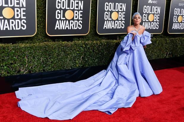 Lady Gaga begeistert bei den Golden Globe Awards alle. Ihr Kleid stammt von Valentino und muss von mehreren Schleppenträgern für Fotos zurecht gelegt werden.