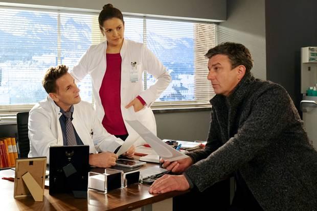 Dr. Fendrich (Rebecca Immanuel, m.), Dr. Kahnweiler (Mark Keller, l.) und Dr. Gruber (Hans Sigl, r.) besprechen die Befunde ihrer Patienten Tom und Hermine.
