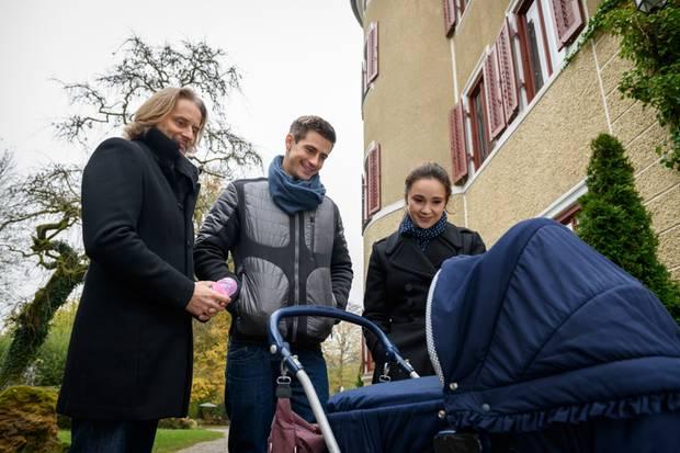 Michael Niederbühl (Erich Altenkopf, l.) zeigt Paul und Romy Pflegekind Felicitas. Handelt es sich bei der Kleinen in Wahrheit um Pauls Tochter?