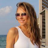 """Das beste Aushängeschild für die Marke Elizabeth Hurley Beach ist wohl die Gründerin selbst. Die Schauspielerin zeigt einmal mehr, wie gut sie in ihrer eigens designten Bademode aussieht. Auf Instagram postet sie ein Foto von sich in einem weißen One-Shoulder-Badeanzug, der den fast schon göttlichen Namen""""Athena One Piece"""" trägt. Das Modell, dass an Athena, die Göttin der Weisheit angelehnt ist,kostet im Onlineshop des Labels 173 Euro."""