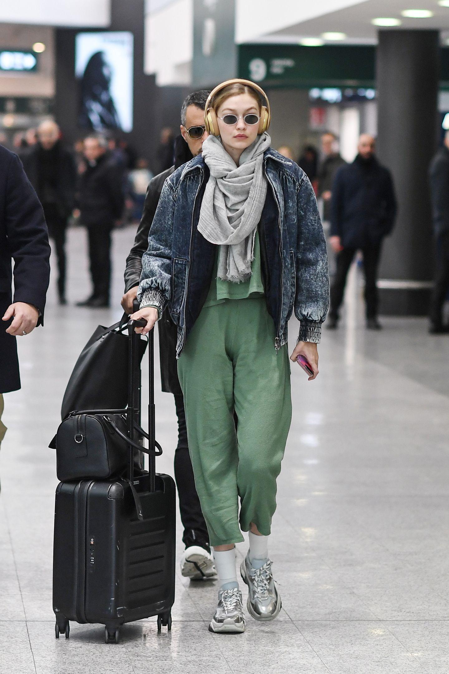 """Bequeme und weite Klamotten sind im Alltag von Gigi Hadid Mangelware: AlsModel präsentiert sie sich häufig in körperbetonten Roben oder in sexy Bademode. Doch auf Reisen kann die 23-Jährige ganz sie selbst sein und hüllt sich in einen weiten, grünen Zweiteiler. Dazu trägt sie eine XL-Jeansjacke im Vintage-Look und einen kuscheligen Schal. Dennoch ist dieser Lässig-Look kein Schnäppchen, denn allein die """"Extreme""""-Sneaker von Ash liegen bereits bei 235 Euro."""
