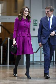 """Was für ein Wow-Auftritt! In einem lilafarbenen Ensemble von Oscar de la Renta besucht Herzogin Catherine das Royal Opera House in London und strahlt über das ganze Gesicht. Den 3.000-Euro-Zweiteiler hatKate in ihrem gut sortierten Kleiderschrank zu Hausegefunden, denn sie wählt ein Kostüm, das die bereits im Februar2017 zu einem öffentlichen Auftritt trägt. Dazu kombiniert die Herzogin schwarze High Heels und eine schwarze Handtasche von """"Aspinal of London"""" für rund 500 Euro."""