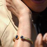 Ein Blick auf die Details: Der goldene Armreifist nicht geschlossen, sondern an beiden Enden mit blauen Edelsteinen versehen. Zusätzlich wird das Schmuckstück mit weißen Diamanten verziert. Auch der Reif an sich mussnicht ohne Schnörkel auskommen - er ist mit zahlreichen Einkerbungen versehen.