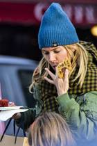 Sienna Miller genießt einen Cookie und schleckt sich die Finger ab.