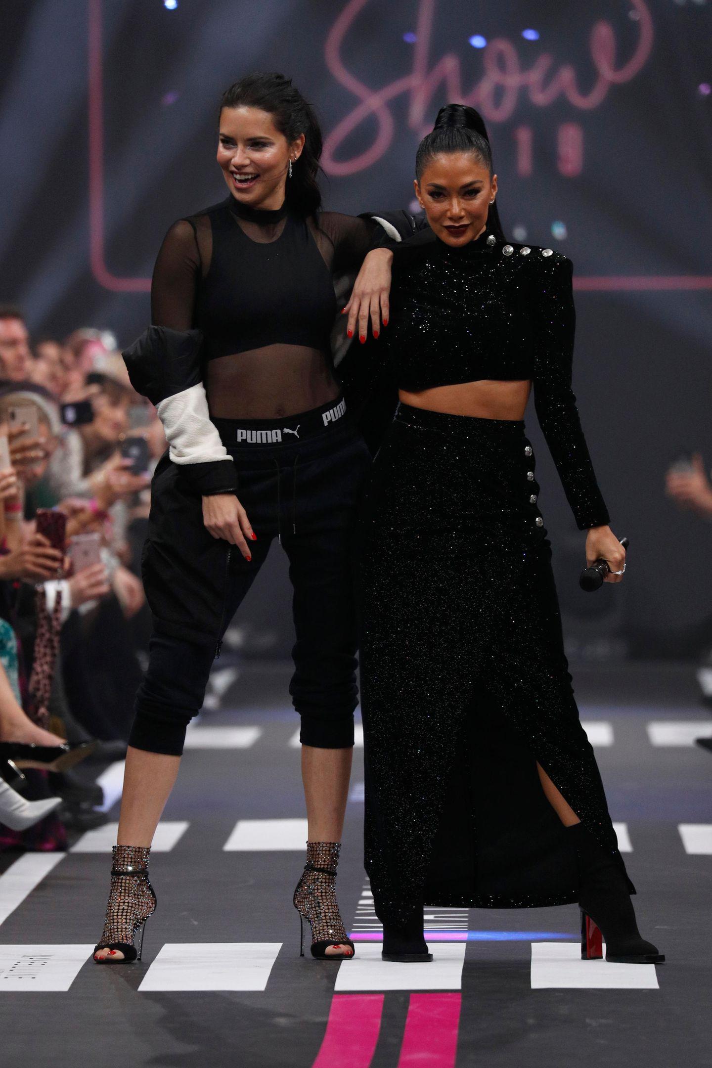 """Maybelline New York schließt die Fashion Week mit einer Mega-Show, bei der zwei der größten Powerfrauen des Showbiz über den Catwalk laufen. Nicole Scherzinger performt """"Don't Cha"""", während Adriana Lima ihren Walk hinlegt."""