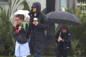 Es gibt kein schlechtes Wetter, es gibt nur falsche Kleidung: Jennifer Garner und die Kinder Seraphina und Samuel machenbei ihrem Weg zur Schule mit den Schirmenund ihrer Regenkleidung jedoch alles richtig.