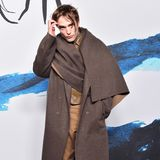 """Men's Fashion Week Paris: Robert Pattinson besucht mit einem überdimensional großen Mantel und leicht verzottelten Haaren die Dior-Fashion-Show in Paris. """"Doppelt hält besser"""", dachte sich wohl der Schauspieler, und trägt zusätzlich unter dem Mantel noch eine Lederjacke."""