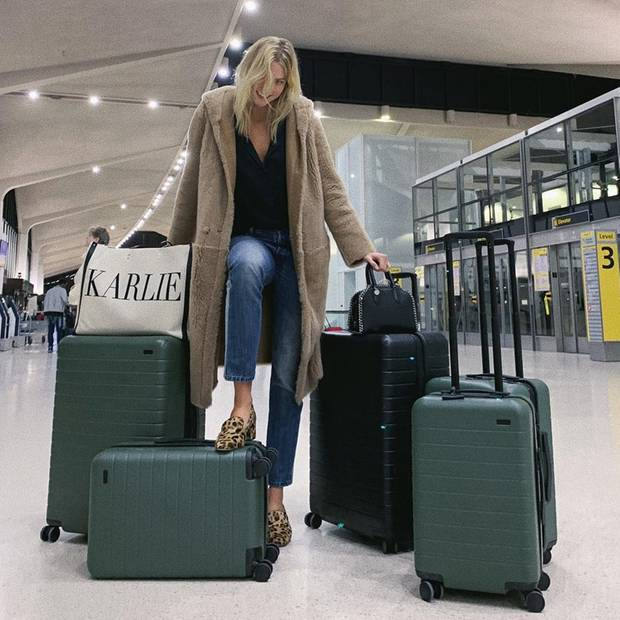 """Gleich mit fünf Koffern und einer personalisierten """"Karlie""""-Tasche macht sich Karlie Kloss auf den Weg zu den Modeschauen nach Paris. Dabei setzt das Model für den Flug auf einen bequemen LookausJeans, T-Shirt und Teddymantel von Max Mara. Dazu kombiniert sie Leo-Loafer mit Blockabsatz."""