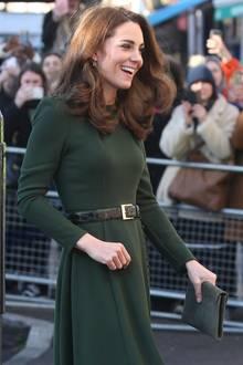Um ihre schmale Taille zu betonen, wählt Catherine einen grünen Gürtel in Schlangenlederoptik und mit goldener Schnalle. Zudem fällt auf, dass das Kleid für sie geändert wurde: Das Original ist mit Trompetenärmeln verziert, Kates Modell kommt jedoch ohne aus. An den Handgelenken ist das Dress dafür mit den gleichen Knöpfen wie am Rock versehen.In der Hand hält die Herzogin eine ebenfalls olivgrüne Clutch aus Wildleder. Die Haare trägt sie offen und gelockt. Obwohl Kate in ihrem All-Over-Grün-Look bezaubernd aussieht, überrascht der Look nicht: Die Herzogin setzt nicht nur auf ihre Lieblingsfrisur, sondern vertraut auch schon seit Jahren auf das Label Beluah London.
