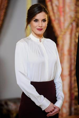 Zu dem auffälligen Rock kombiniert Letizia eine schlichte weiße Bluse von Hugo Boss, die man schon des Öfteren an ihr bewundern konnte. Auch die Haare passen zu dem schicken Stil der Bluse: Letizia trägt einen strengen Dutt, der durch eine herausfallende Strähne etwas aufgelockert wird.  Ihr aufregendes Make-up passt sich wieder dem Rock an. Die Königin betont ihre Lippen mit einem dunkelroten Lippenstift, ihre Augen sind ebenfalls dunkel geschminkt.