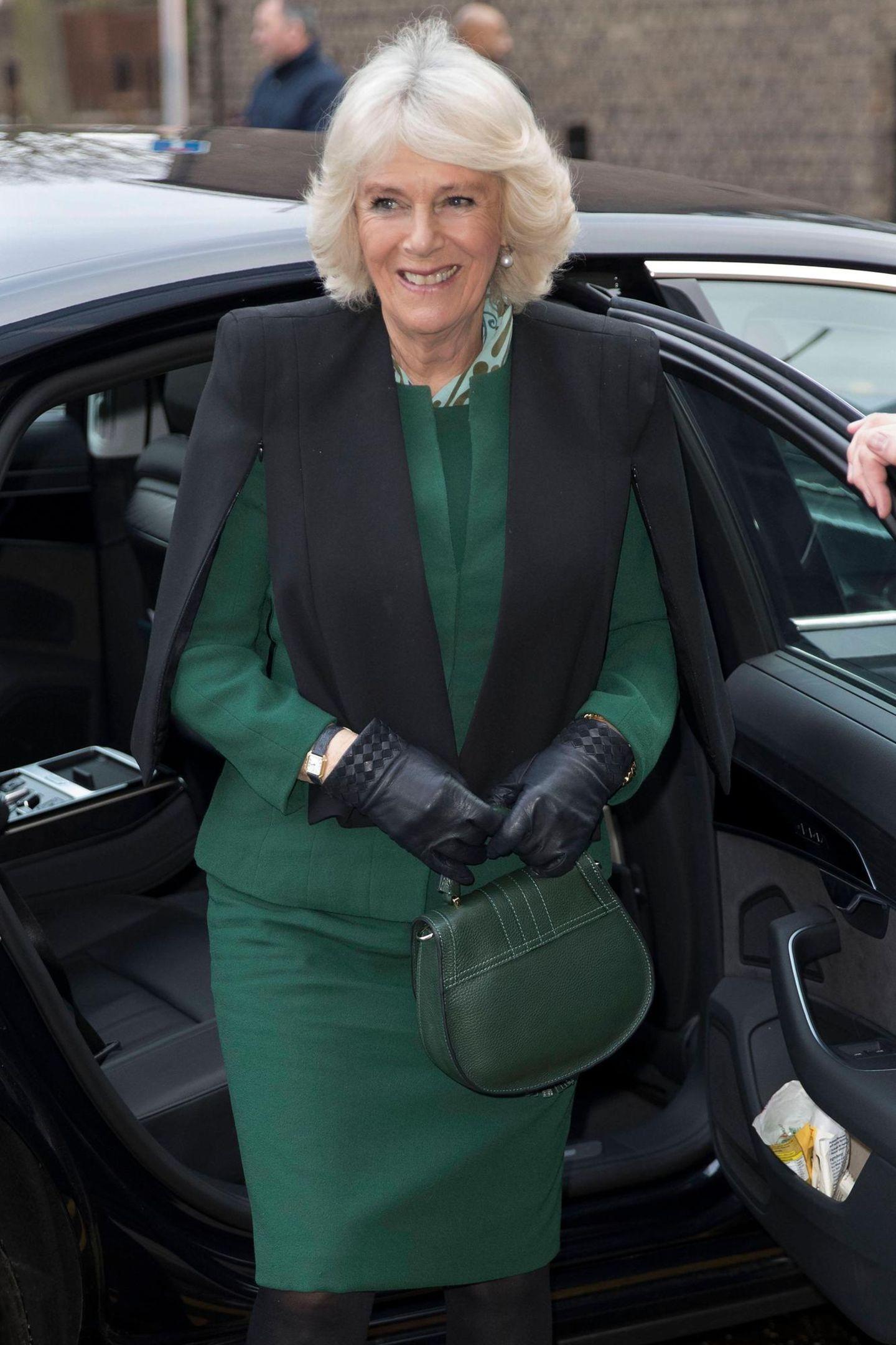 """Als Herzogin Camilla beider """"Malmesbury Residents Association"""" aus dem Auto steigt fällt nicht nur auf, dass die Royals aktuell die Farbe Grün lieben, sondern auch den gleichen Handtaschen-Geschmack haben. Denn Camillas Tasche, die den Namen """"The Mini Venice"""" trägt, kommt uns extrem bekannt vor."""