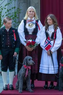 Anlässlich des norwegischen Verfassungstags am 17. Mai 2018 zeigt sich Ingrid Alexandra in einer ganz ähnlichen Tracht wie Mutter Mette-Marit. Beide Prinzessinnen verzieren die traditionellen Kleider mit auffälligen goldenen Broschen. Die Haare trägt Ingrid Alexandra offen, zusätzlich hat sie ein leichtes Tages-Make-up und Wimperntusche aufgelegt.
