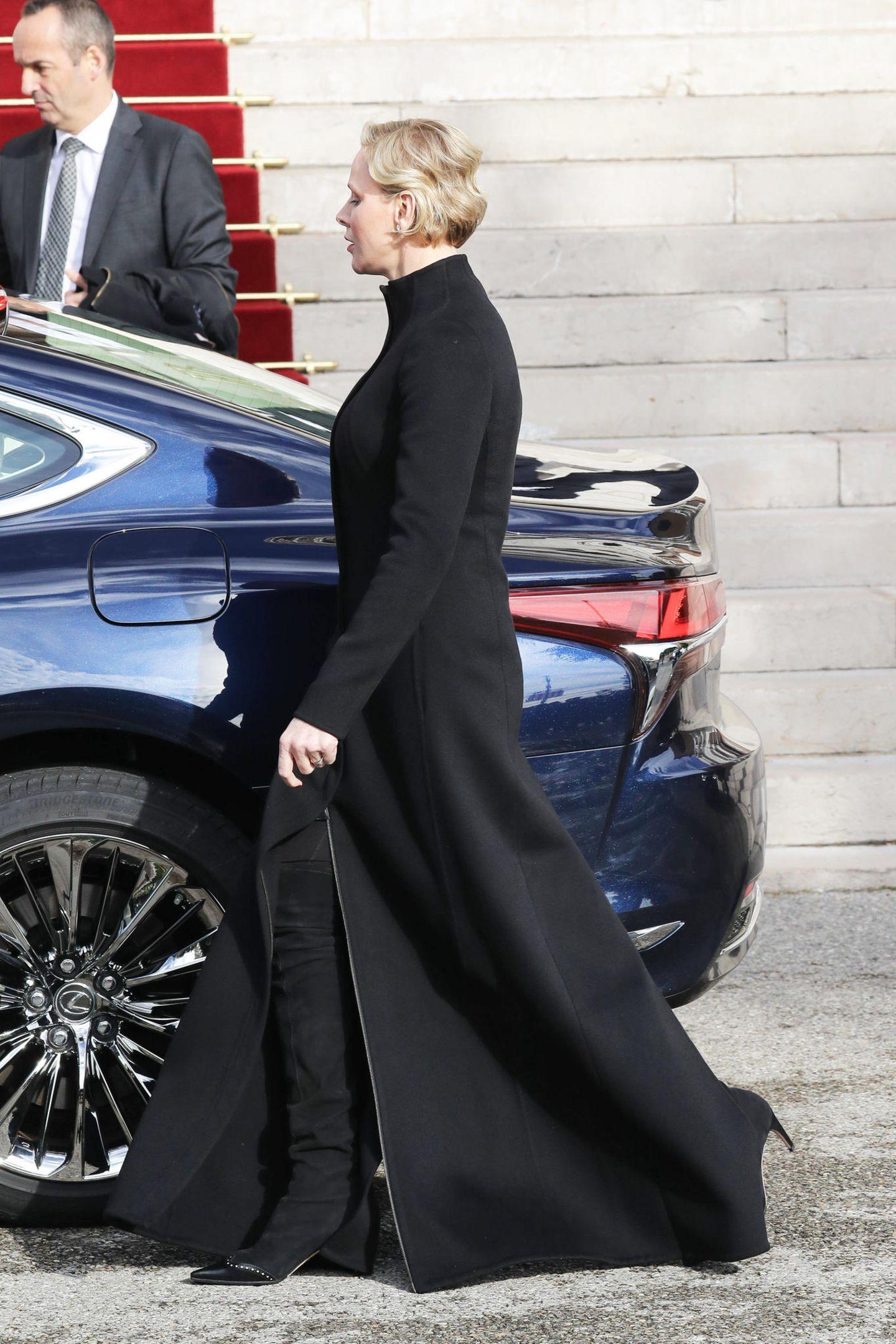 Unter dem Mantel trägt Charléne schwarze Wildleder-Overknees, die den eher fraglichen Look zusätzlichunterstreichen.