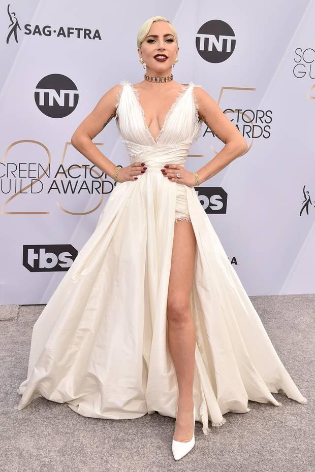 Lady Gaga ist sich der Schönheit ihres Couture-Kleides von Christian Dior bewusst und posiert darin äußerst stolz.