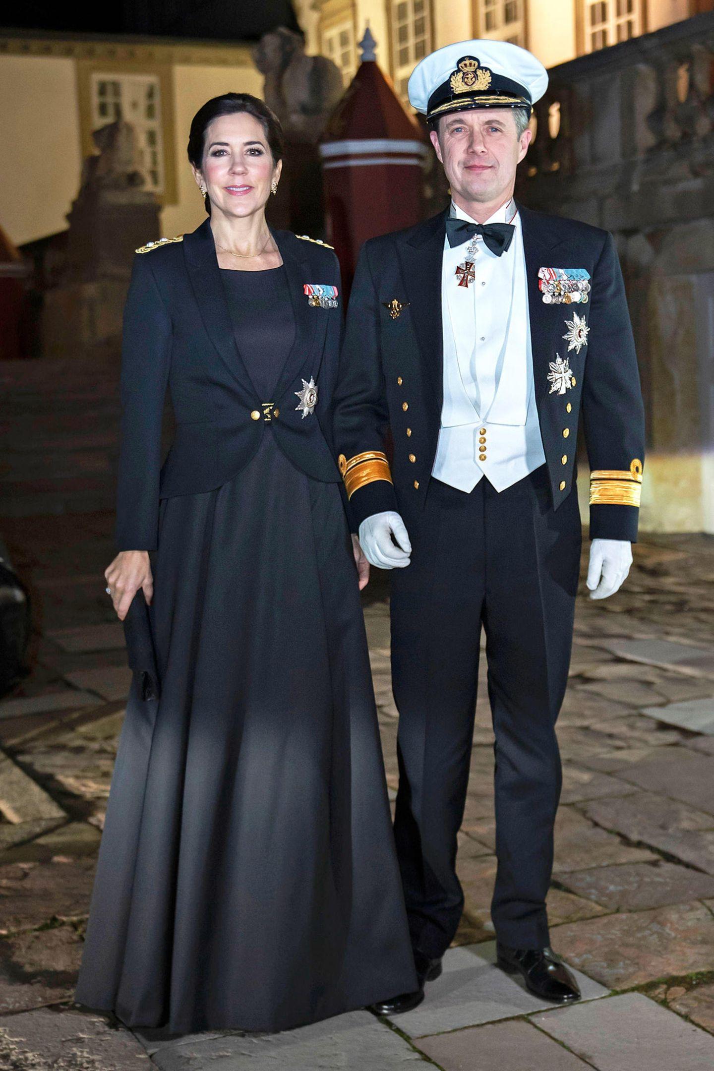 Prinzessin in Uniform: Mary bezaubertbeim Ehrendinner für die Marineoffiziere auf Schloss Fredensborg in der neuen Ausgehuniform für Frauen in der Armee. Das schwarze Abendkleid aus einem Satin-Wolle-Gemisch wird mit einem goldenen Gürtel mit Eichen-Motiv und einem passenden Blazer samt Schulterklappen und Orden getragen.