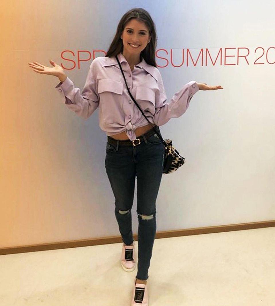 Ist denn schon wieder Sommer? Auf der Stoffmesse in München präsentiert sich Cathy Hummels gut gelaunt im bauchfreien Blusen- und Jeans-Look.