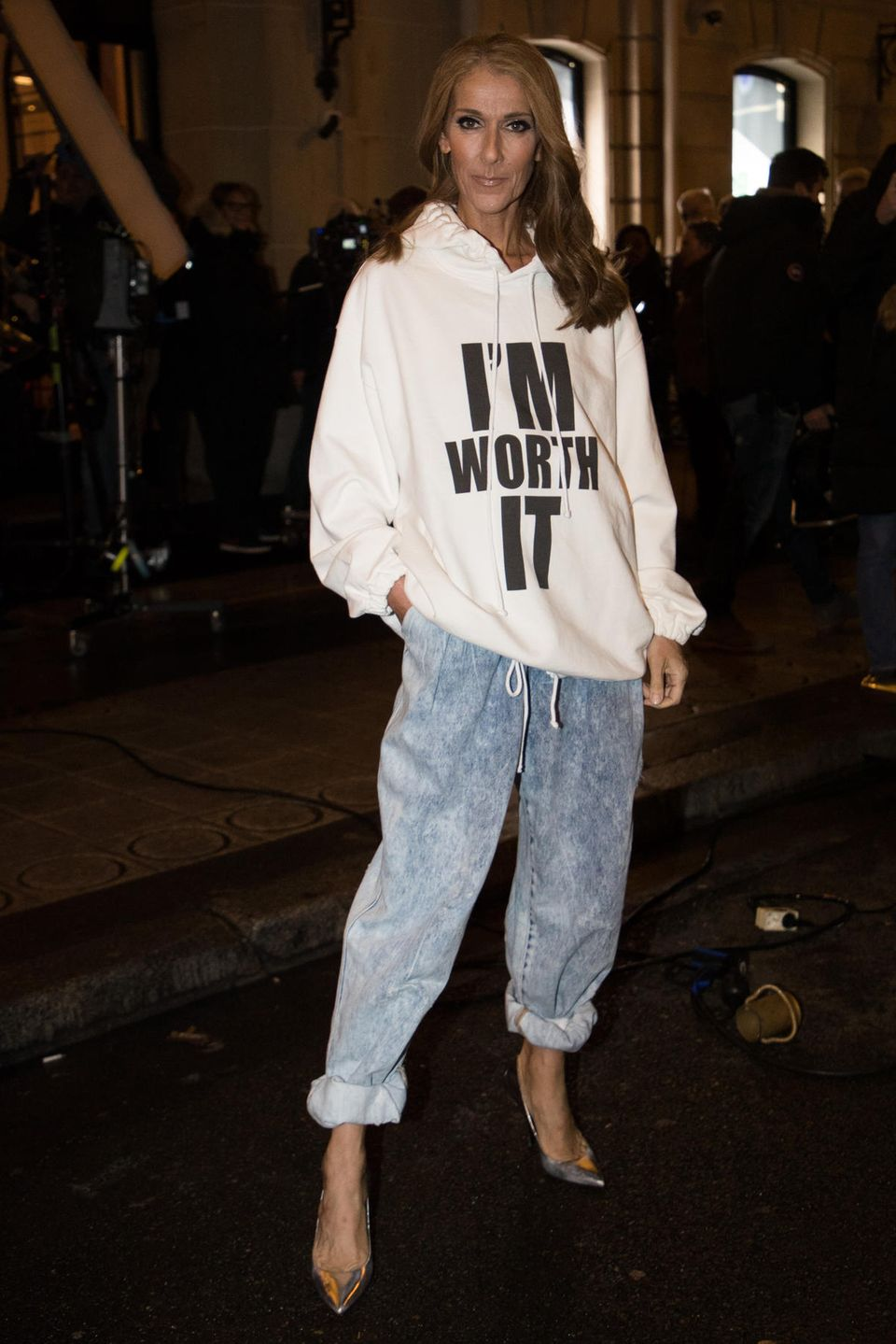 """Was es mit dieser Botschaft wohl auf sich hat? Céline Dion zeigt sich in Paris mit einem Statement-Hoodie. Nicht nur das Design des auffälligen Pullovers ist bemerkenswert, auch die Botschaft hat es in sich. """"I'm worth it"""" (zu dt.: Ich bin es wert) prankt in großen, schwarzen Lettern auf ihrem weißen Oberteil.Zu dem Oversize-Pulli kombiniert Céline eine ebenfalls übergroße Jeans und Pumps. Klarheit bezüglich dieses auffälligen Looks verschaffen jedoch die folgenden Bilder..."""