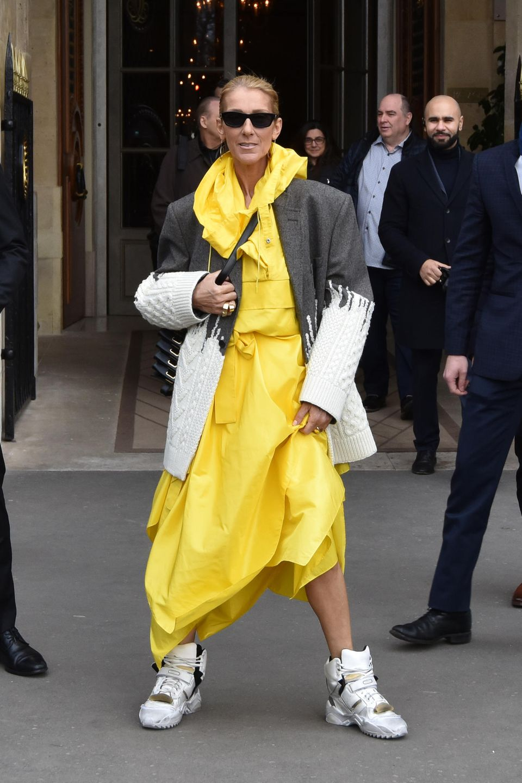 Ob Céline Dion eine Sonnenbrille trägt, um sich vor ihrem strahlenden Kleid zu schützen? Vor dem Shooting zeigt sie sich nämlich noch in einem ganz anderen Look. In einem knallgelben Kleid mit Kapuze, das etwas an einen Regenmantel erinnert, macht sie sich auf den Weg zur Location. Zu dem auffälligen Dress kombiniert sie klobige Sneaker in Weiß und Gold sowie einen Oversize-Blazer in Grau mit weißen Strickeinsätzen.