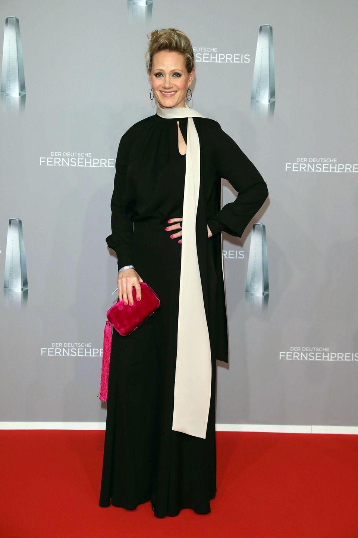 Anna Schudt setzt im elegantenAbendkleid kombiniert mitpinkfarbener Clutch auf einen knalligen Kontrast.