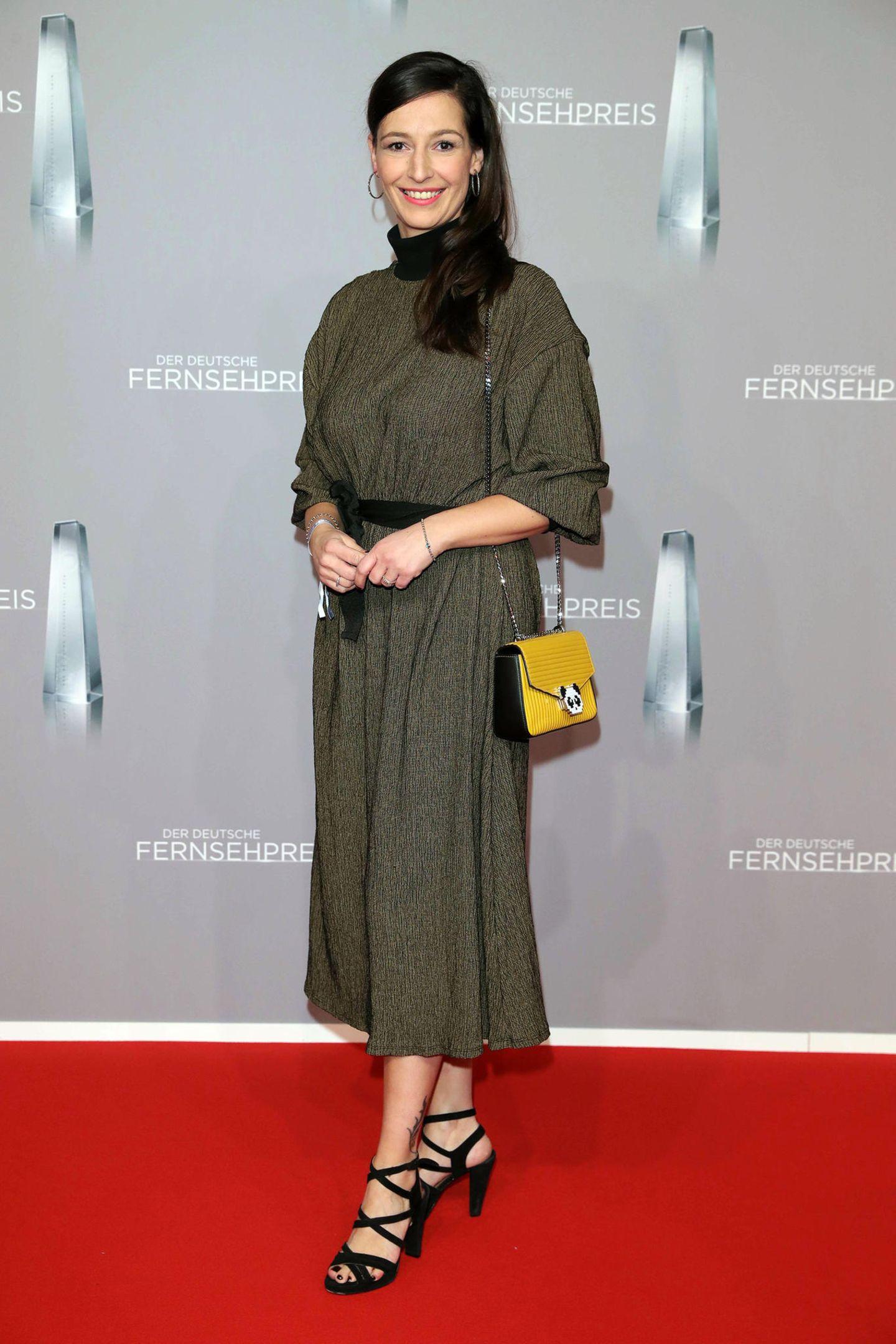 Moderatorin Pinar Atalay setzt mit ihrer gelben Handtasche zum khakifarbenen Dress einen kleinen farblichen Akzent.
