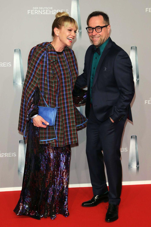 Anna Loos, mit Karo-Cape und changierendem Pailletten-Kleid, und Jan Josef Liefers gefallen uns in diesem farblichen Partnerlook besonders gut.