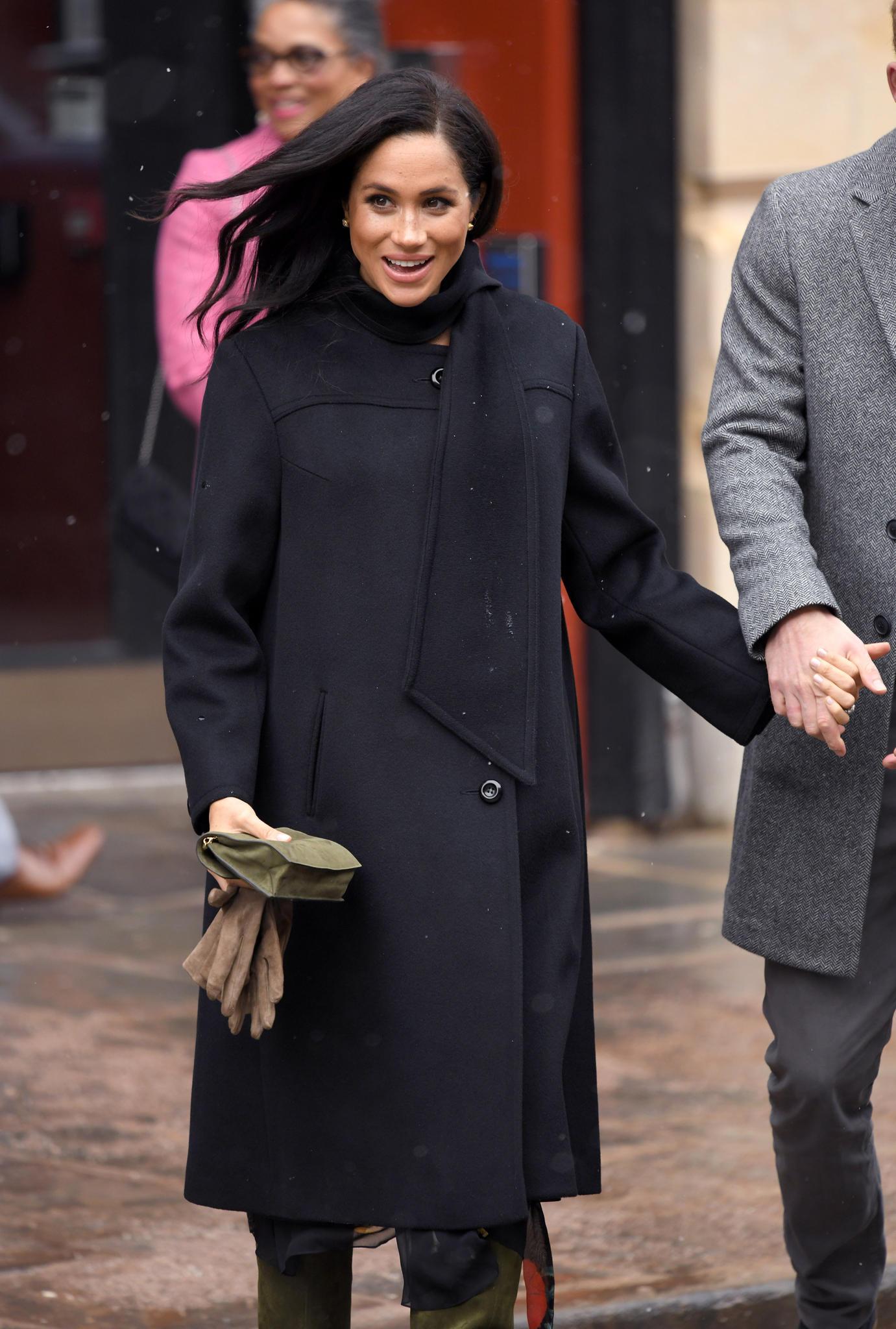 Herzogin Meghan hält ihre beigefarbenen Handschuhe in der einen und Prinz Harry an der anderen Hand.