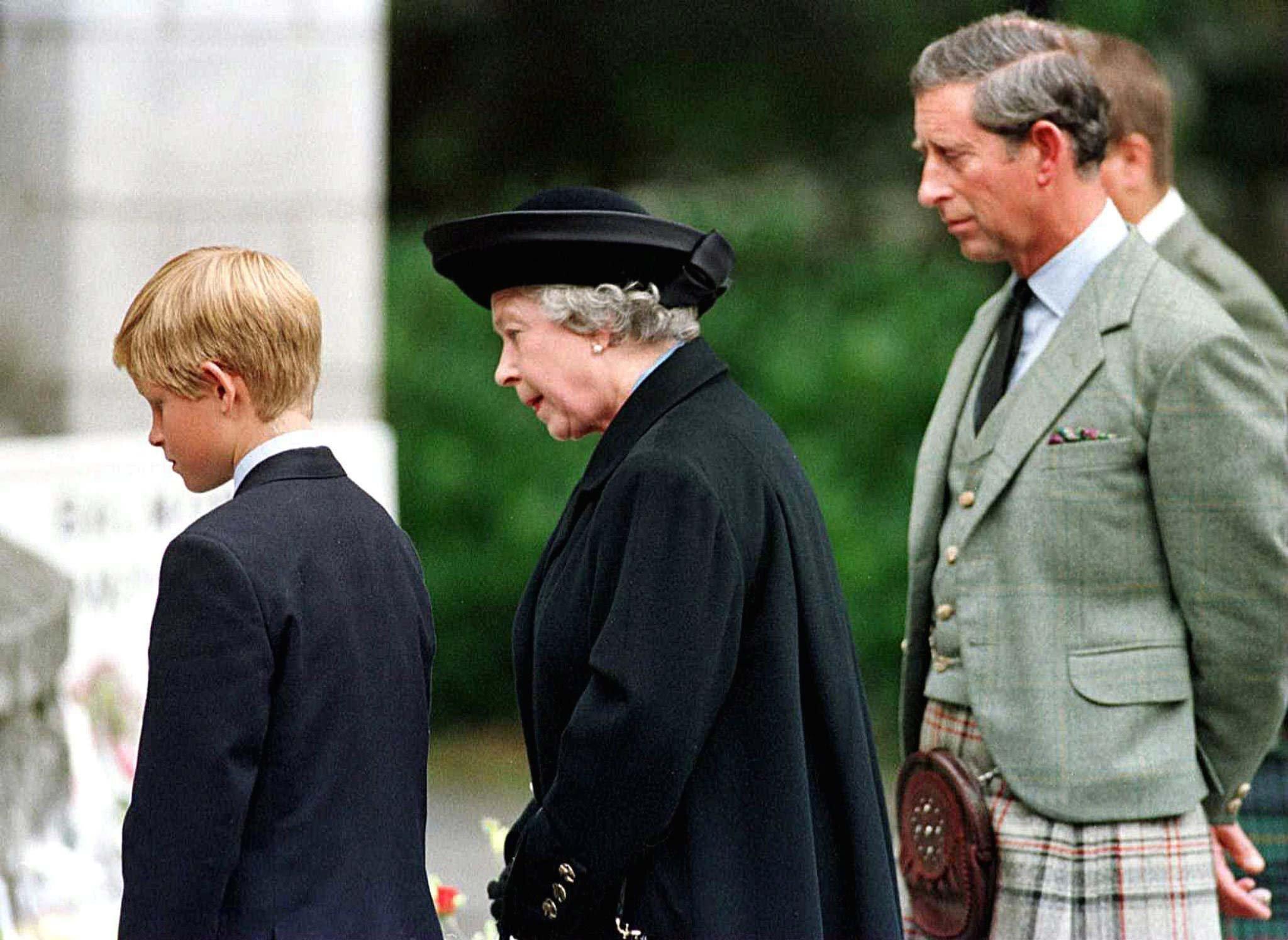 Prinz Harry (l.), Queen Elizabeth (M.)und Prinz Charles (r.) betrachten am 4. September1997 vor den Toren von Schloss Balmoraldie Blumenspenden, die für Prinzessin Diana niedergelegt wurden