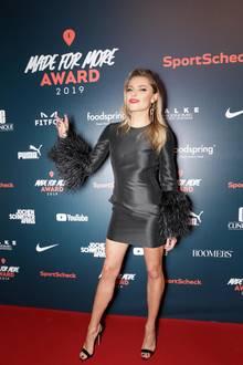"""In einem knappen, schwarzen Kleid mit Federärmeln posiert Sophia Thomalla auf dem roten Teppich der """"Made for More""""-Awards in München. Als farblichen Akzent trägt sie roten Lippenstift."""