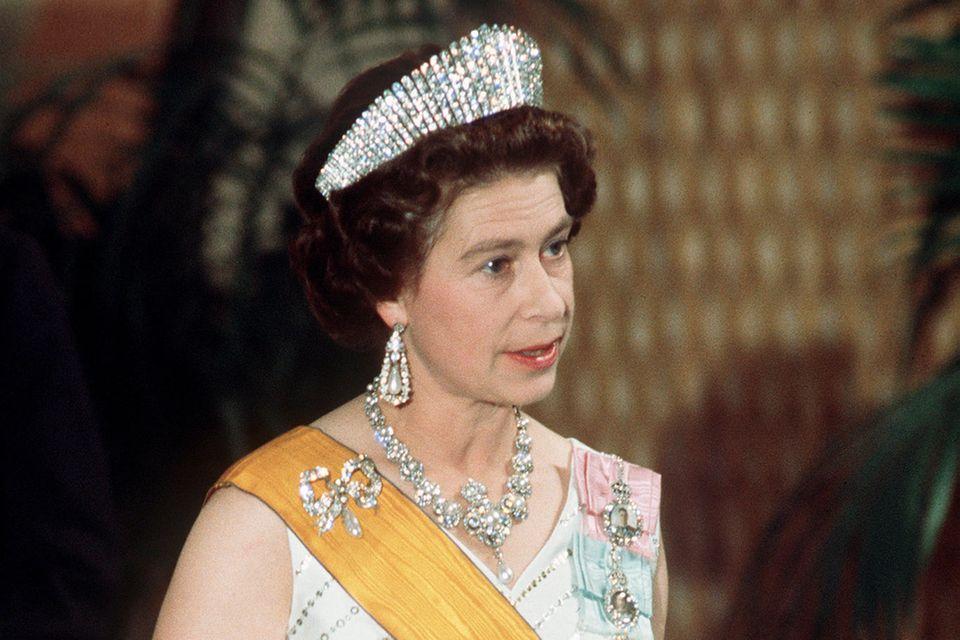 Abends trägt die Queen, die während ihrer Termine viele Hände schütteln muss, meist Nylon-Handschuhe. Seit 1947 setzt sie auf das britische Label Cornelia Lawson - so wie hier 1975.