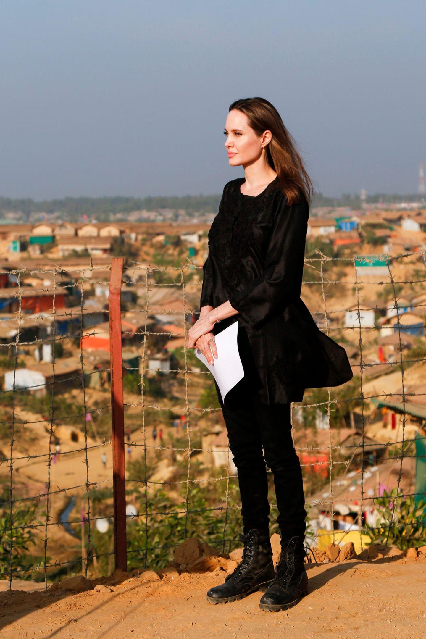 Es ist ein öffentlicher Auftritt, der Angelina Jolie besonders am Herzen liegt: In Bangladesch besucht die UN-Sonderbotschafterin ein Rohingya-Flüchtlingslager, wo sie eine Rede hält. Zur Pressekonferenz erscheint die 43-Jährige ganz in Schwarz: Zu einer seidenen Tunika mit bestickten Ornamenten trägt sie eine schmale Jeans, deren Endenin derben Boots verschwinden.
