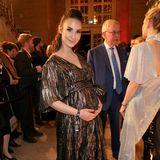Die Babykugel in sicheren Händenzeigt sich Schauspielerin Sila Sahin lächelnd im Trubel des Eingangsbereichs.
