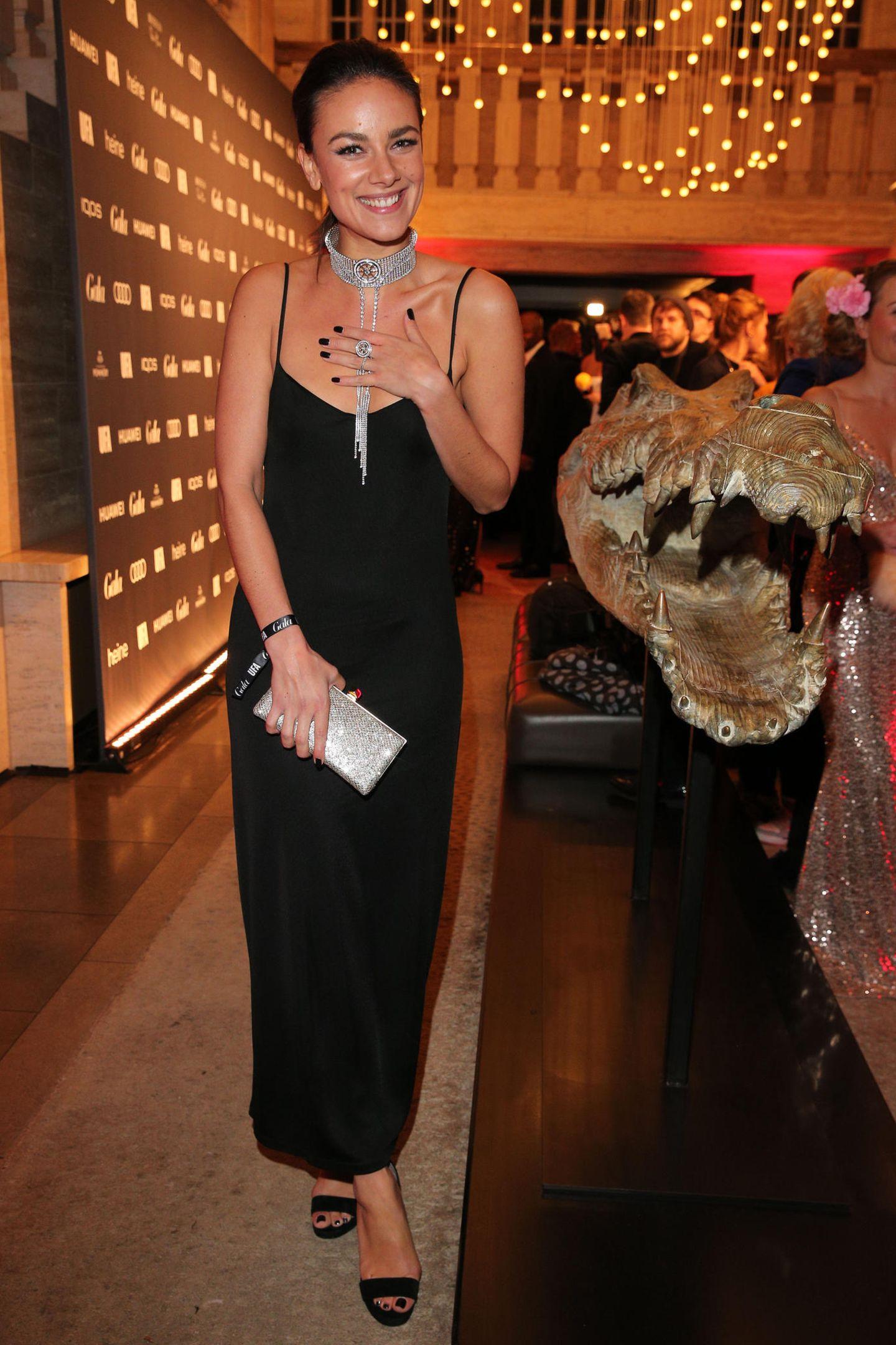 SchauspielerinJanina Uhse neben einschüchternder Dekoration.