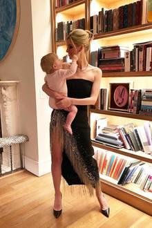 Während Söhnchen Teddy versucht Mama Nicky Hiltons Diamanten-Ohrringe zu stibitzen, zeigt sich im Hintergrund ein Teil des luxuriösen Wohndomizils. Ein großes Bücherregal, der Kamin und ein Kunstwerk schmücken den Raum. Der gemütliche Holzfußboden rundet das Ganze ab.