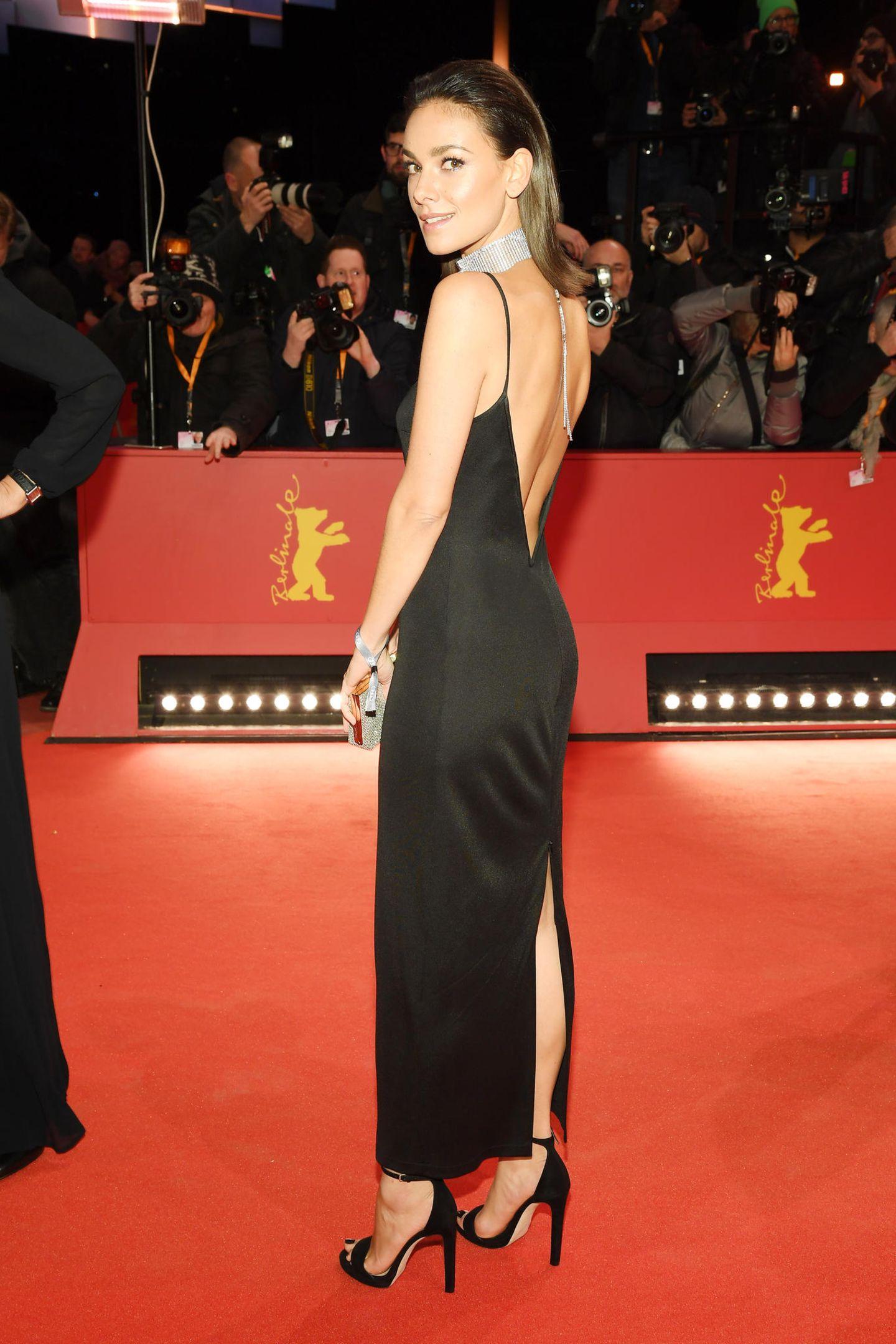 In einem schwarzen, schlichten Slip-on-Dress beweist Janina Uhse ihr großartiges Gespür für Mode. Den passendenGlam-Faktor erhält das Outfit der hübschen Schauspielerin durch den opulenten Choker in Strass-Optik und den tiefen Rückenausschnitt, den sie gekonnt einzusetzen weiß.