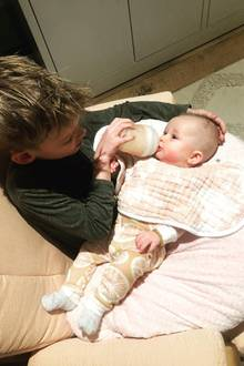 """Geschwisterliebe wie sie im Buche steht! Hilary Duffs Sohn Luca füttert seine kleine Schwester Banks mit dem Fläschchen. Damit sie besonders gut trinken kann, hat er sich die Kleine auf den Schoß gelegt und stützt ihren Kopf liebevoll mit einer Hand. Mama Hilary fängt diesen zuckersüßen Moment für Instagram ein und kommentiert diesen mit dem einfachen Wort """"Geschwister""""."""