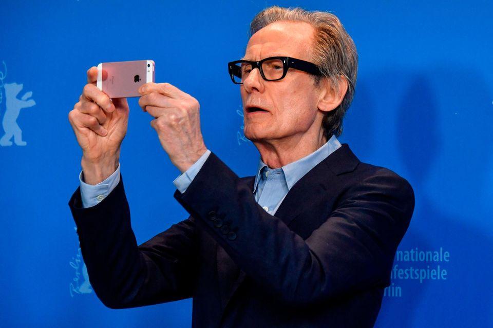 """Schauspieler Bill Nighy versucht sich bei dem Pressetermin zum Eröffnungsfilm """"The Kindness of Strangers"""" als Paparazzi und hält das Geschehen mit seinem Handy fest."""