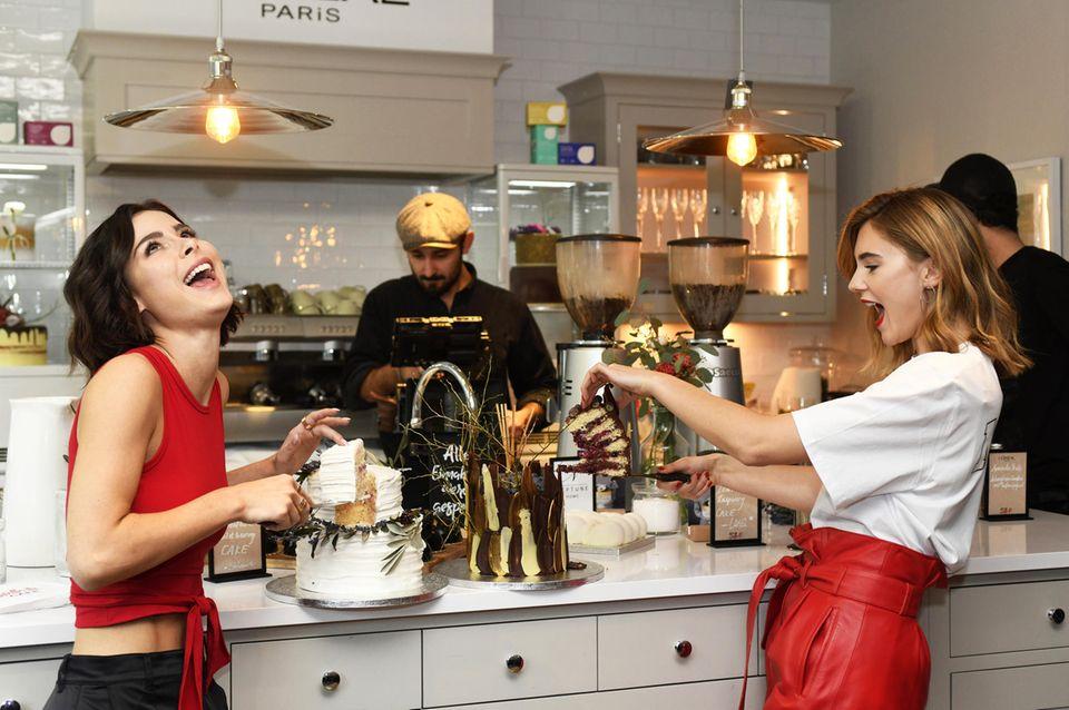 Lena Meyer-Landrut und Stefanie Giesinger schneiden bei der Eröffnung des worth it! Cafés by L´Oréal Parisihre Torten an.