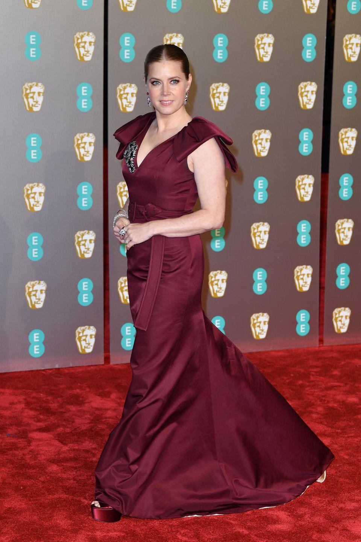 Amy Adams glänzt in einer weinroten Prada-Robe. Ihr Statement-Schmuck ist von Cartier.