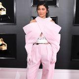 Der Anzug stammt von Balmain, Olivier Rousteing gehört zu den Lieblingsdesignern der Kardashians. Während seine Designs sonst figurbetonend und formgebend sind, wirft diese Kreation mit Handschuhen und Wickelärmeln viele Fragen auf.