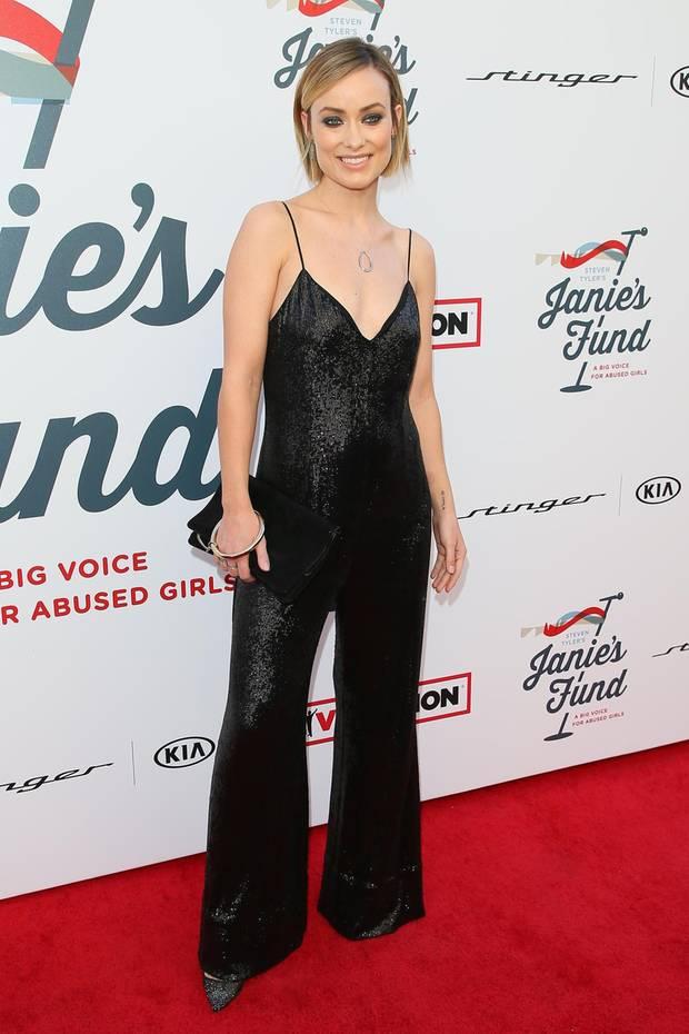 Bei der Grammy-Awards-Party von Steven Tyler feiert Olivia Wilde in einem Pailletten-Jumpsuit mit, derfeine Träger hat und dessen Hosenbeine mit einem leichten Schlag besonders schick wirken.