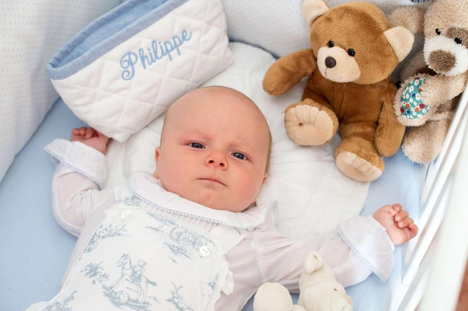 Der kleine Prinz in seinem Bett: Ganz wach und ernst schaut Philippe, der am 22. Oktober getauft wurde, bei seinem ersten Fototermin in die Kamera.