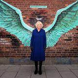 """In Liverpool wird Herzogin Camilla einmal mehr ihrem Ruf gerecht, dass sie regelmäßig lustige Fotomotive bietet. Bei ihrem Besuch in der Jamaica Street posiert die Herzogin von Cornwall vor dem berühmten Wandgemälde """"For all Liverpool's Liver Birds"""", das aus der Feder des KünstlersPaul Curtis stammt. Apropos Feder: Camilla posiert, wie so viele Touristen auch, inmitten der aufgemalten Flügel, lässt sich vor der Backsteinwand wie ein Engel ablichten und sorgt damit mal wieder für einen herrlich lebensnahen Moment.  Das gefällt auch den Fans der Herzogin, die das Bild bei Instagram mit dem niedlichen Kommentar """"Charlie's Angel"""" direkt auf Prinz Charles beziehen."""